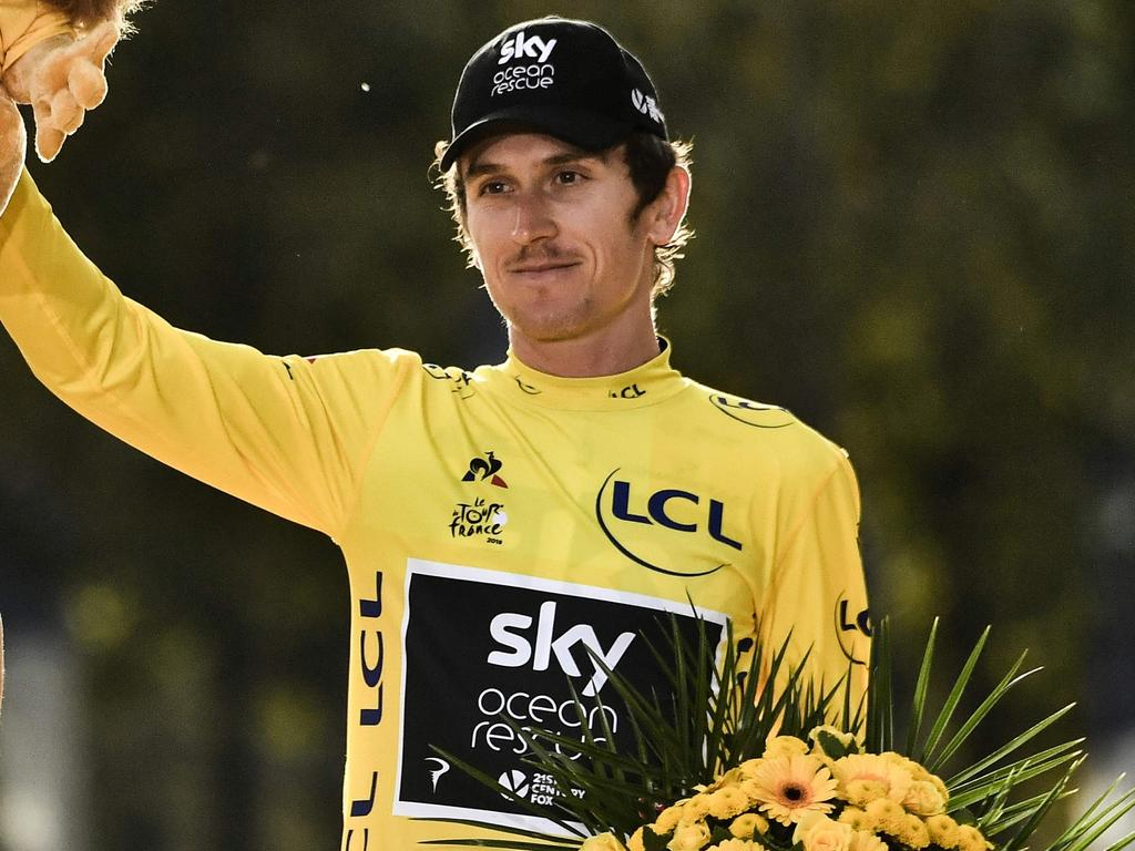Tour de France 2018 winner Great Britain's Geraint Thomas (C) celebrates his overall leader yellow jersey on the podium after the 21st and last stage of the 105th edition of the Tour de France cycling race between Houilles and Paris Champs-Elysees, on July 29, 2018. / AFP PHOTO / Marco BERTORELLO