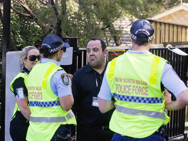 Police talk to security as staff members avoid the media. Picture: Jenny Evans