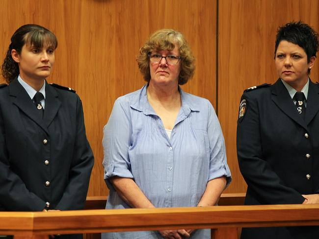 Helen Milner stands between two police officers at her murder trial.