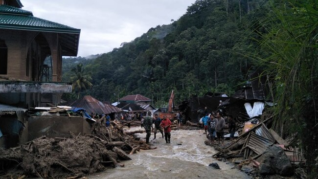 Villagers wade through flood water at the Saladi village in Mandailing Natal, North Sumatra. Picture: Agus Salim / AFP