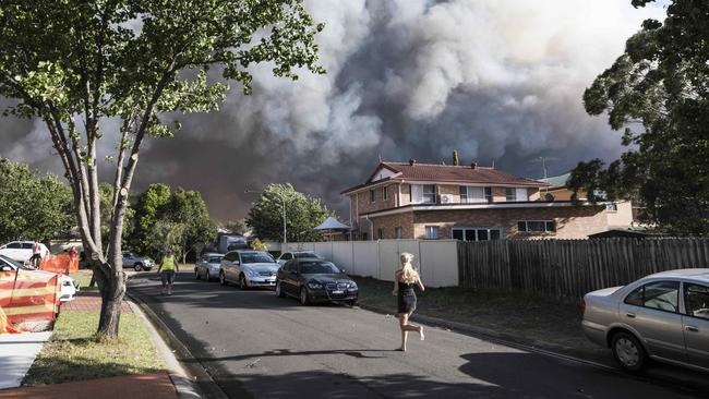 A resident runs along a street as the fire takes hold. Picture: Darren LeighRoberts