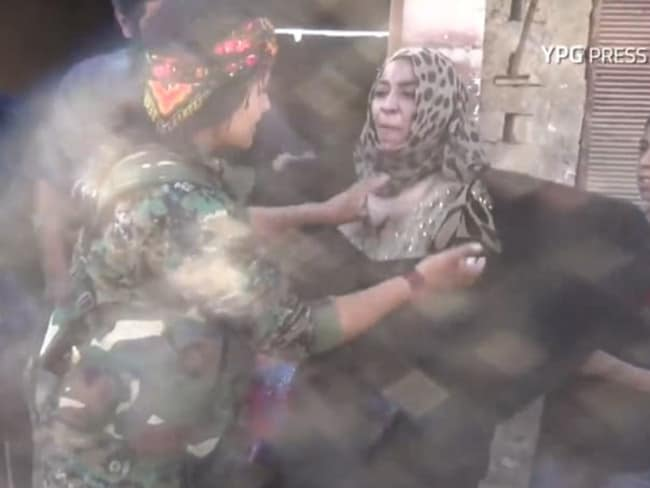 The woman rips off her clothes that she was forced to wear under Islamic State rule.