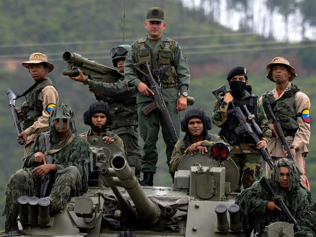 Venezuelan troops in different fatigues and carrying various weapons stand on a Russian-made BMP-3M IFV. Picture: AFP / Federico Parra