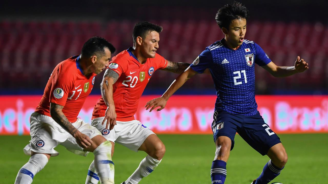 Japan's Takefusa Kubo(R) is chased by Chile's Charles Aranguiz(C) and Chile's Gary Medel