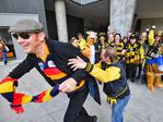 A Crows fan crashes a Tigers supporters' photo. Picture: Jason Edwards