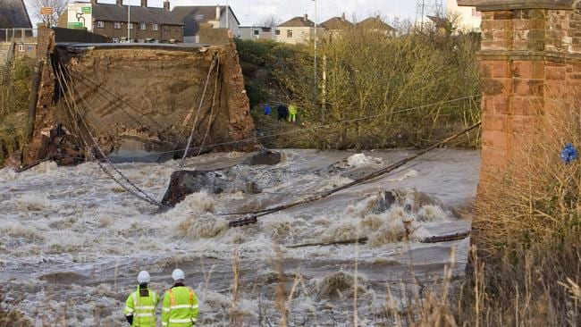 Engineers survey the scene after a bridge over the River Derwent collapsed after heavy rainfall and flooding in Workington, England.