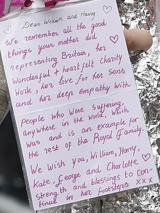 Prince William takes flowers and notes from the public which he placed among other tributes. Picture: AP