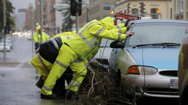 Crews clear debris left by overnight floods on Macquarie St, Hobart flood cleanup. Picture: MATHEW FARRELL