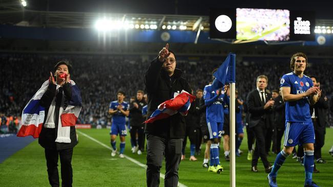 Apichet Srivaddhanaprabha (L) and Aiyawatt Srivaddhanaprabha (C) the sons of Leicester City's late Thai chairman Vichai Srivaddhanaprabha applaud the fans