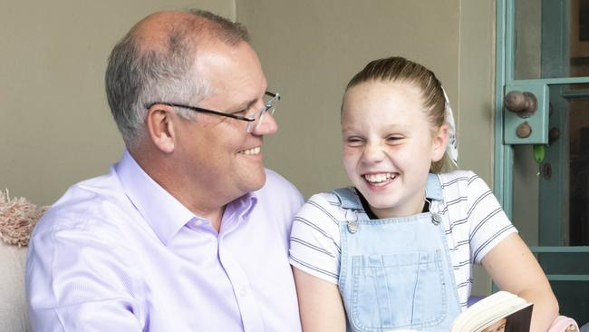 Prime Minister Scott Morrison enjoys a special moment with his daughter Abbey as they read together. Picture: Darren Leigh Roberts