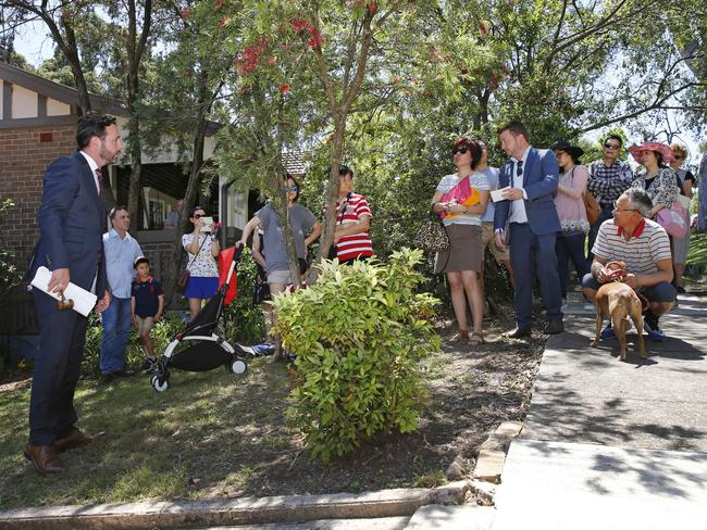 Auctioneer Ben Mitchell addresses the small crowd that had gathered in the street for the auction. Picture: Richard Dobson