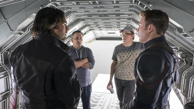 Sebastian Stan as the Winter Soldier, directors Joe and Anthony Russo and Chris Evans as Captain America on set.