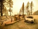 """A burnt car and a gas station remain visible after the """"Camp"""" fire tore through the region near Pulga, east of Paradise, California on November 11, 2018. Picture: Josh Edelson / AFP"""