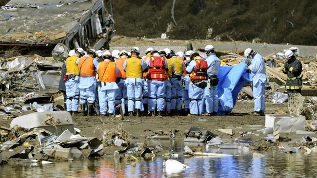 Firefighters and rescuers pray in front of the body retrieved from the rubble in Rikuzentakata, northern Japan Friday, March 18, 2011, one week after a massive earthquake and tsunami /AP