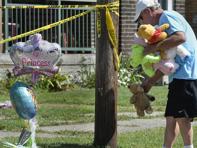 Paul Laughlin places stuffed animals outside the home in Pennsylvania where five children died in a fire. Picture: AP