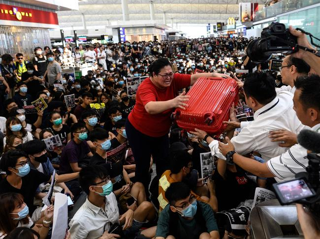 A tourist gives her luggage to security guards as she tries to enter the departures gate during another demonstration by pro-democracy protesters at Hong Kong's international airport. Picture: Philip Fong/AFP