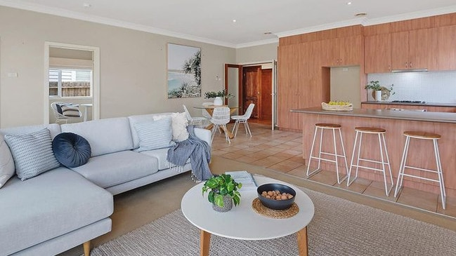 The open-plan living areas flow out to a rear deck.