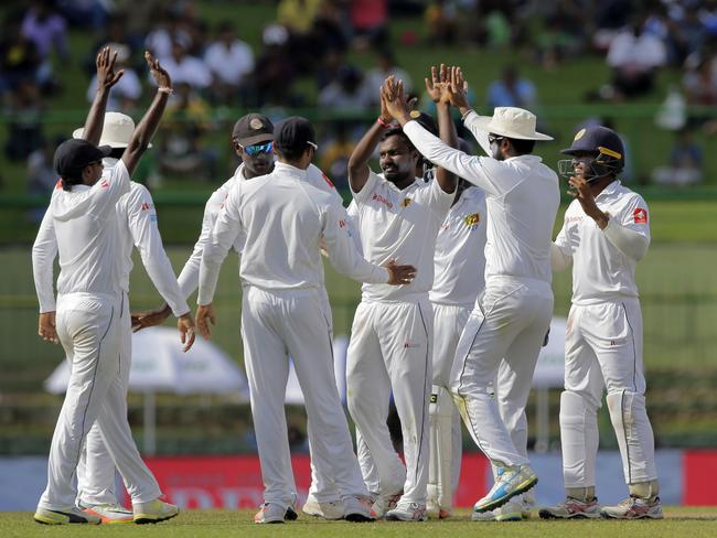 Sri Lanka's Malinda Pushpakumara, centre without cap, celebrates with teammates the dismissal of India's Ajinkya Rahane.