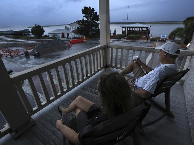 Managers Matt and Janet Kircher, who decided to ride out the storm, watch the approachment of Hurricane Dorian at sunrise from the porch of the Riverview Hotel in St. Mary's, Georgia. Picture: Curtis Compton/Atlanta Journal-Constitution via AP