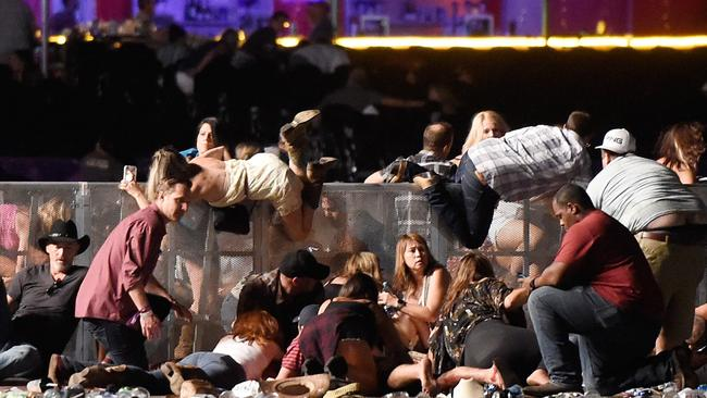 Music fans try to scramble over a barrier at the Route 91 Harvest Festival. Picture: David Becker