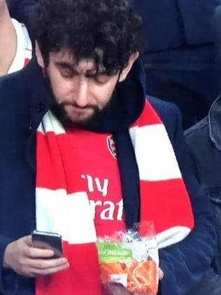 An Arsenal fan munches on a bag of carrots.