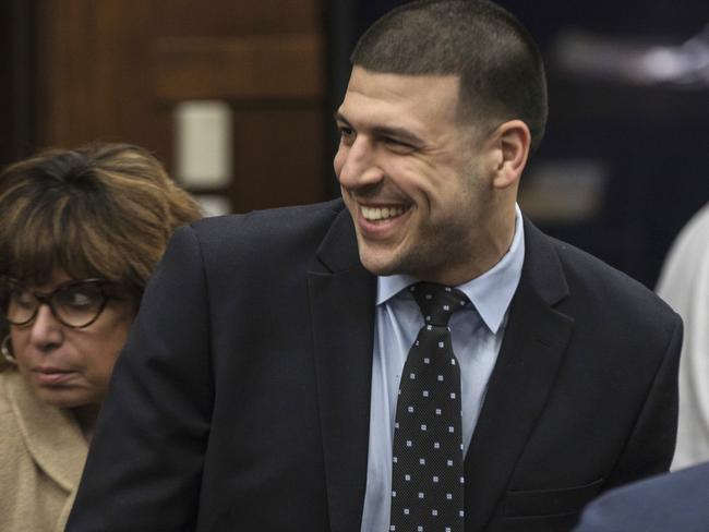 Former New England Patriots tight end Aaron Hernandez smiles at the sight of his fiancee Shayanna Jenkins Hernandez, who brought the couple's daughter to court. Picture: AP