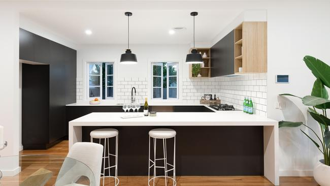 The kitchen has white subway tiles mixed with black, white and timber cabinetry.