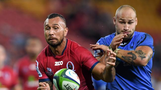 Quade Cooper of the Queensland Reds protects the ball from Billy Meakes of the Force.