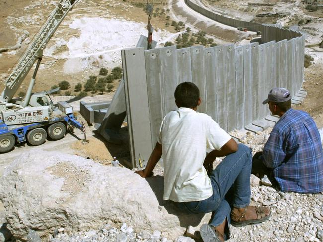 Palestinians watching workers install cement blocks pillars, building separation barrier wall in Abu Dis, Jerusalem, in 2004. Picture: Supplied
