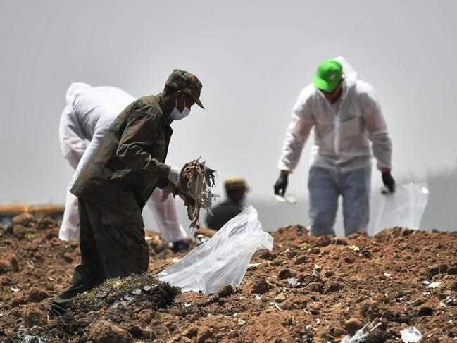 Forensics experts comb through the dirt for debris at the crash site. Picture: Tony Karumba/AFP