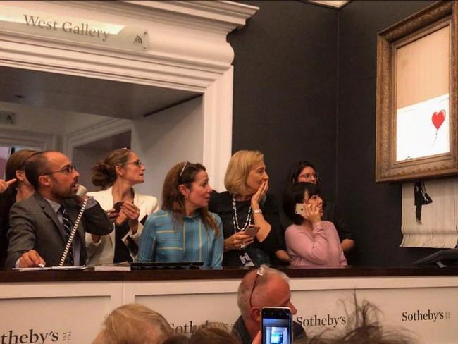 Just after the hammer came down, the bottom half of the work passed through a shredder concealed in the frame. Sotheby's the painting is being sold with a new title, Love Is In The Bin. Picture: AP