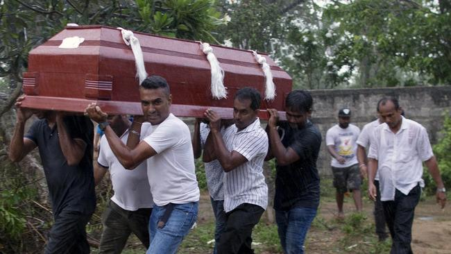 Relatives carry a coffin during the funerals of three people of the same family who were killed in the bombings. Picture: AP