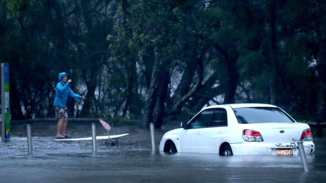 A person on a paddle board on a flooded Goodwin Street Narrabeen near Narrabeen lagoon. Picture: Damian Shaw