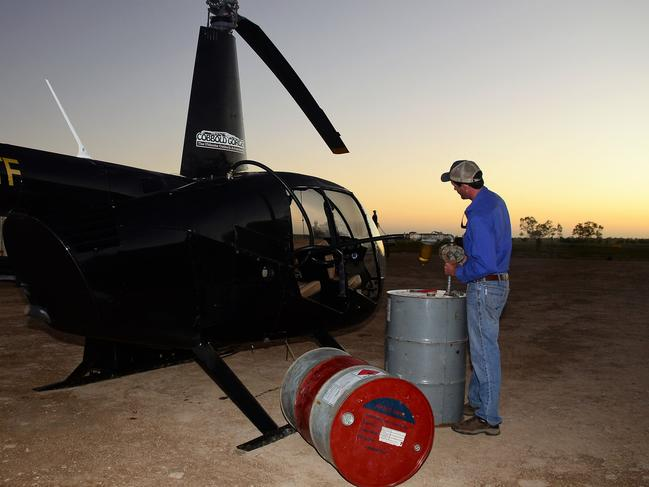 Flood relief helicopter pilot Harry Terry from Forsayth pumps fuel into his chopper before heading to Julia Creek. Picture: John Andersen