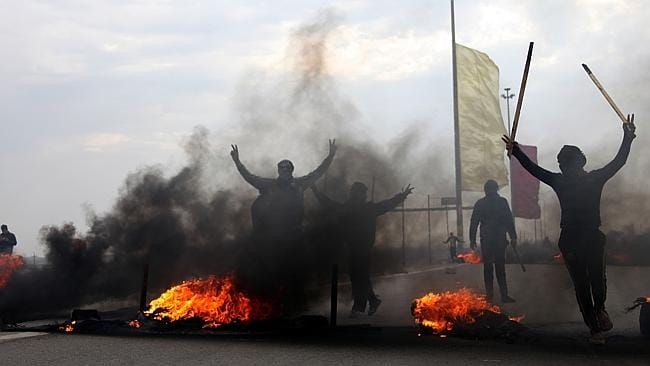 Protesters burn tires to block one of the main highways outside Fallujah, Iraq. Picture: AP