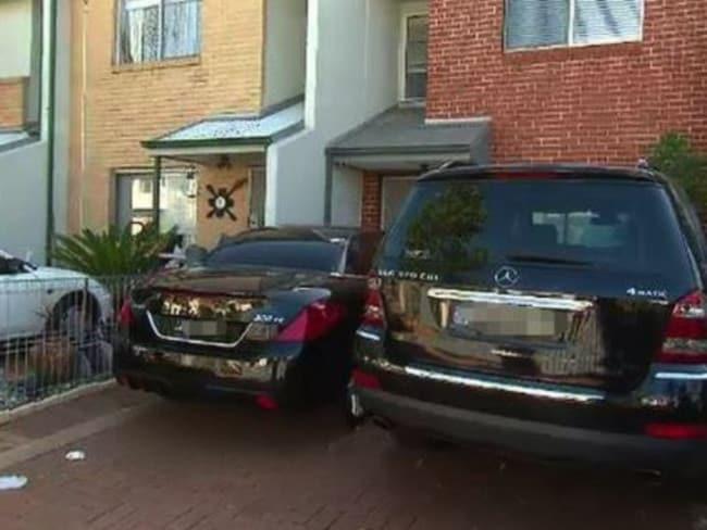 Luxury vehicles parked outside public housing.