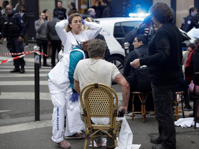 An injured man is treated by emergency workers after the explosion of a bakery. Picture: AFP