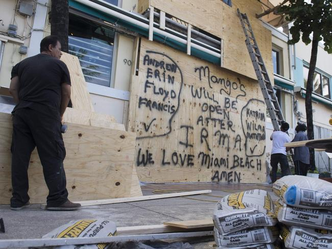 Workers hang plywood in front of doors and windows at salsa club Mango's following mandatory evacuation orders in Miami Beach, Florida. Picture: Saul Loeb/AFP
