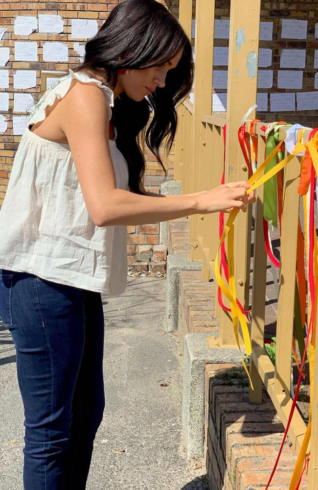 Meghan, Duchess of Sussex ties on a ribbon as she visits the memorial to murdered South African student Uyinene Mrwetyana in Cape Town. Picture: Instagram/Sussex Royal/AFP