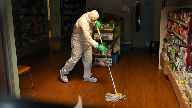 A worker in protective clothing cleans the floor of the pharmacy attached to the the County Oak Medical Centre in Brighton, southern England. Picture: Glyn Kirk / AFP