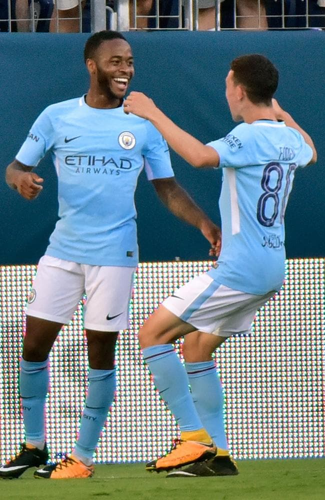 Raheem Sterling #7 of Manchester City is congratulated by teammate Phil Foden #80.