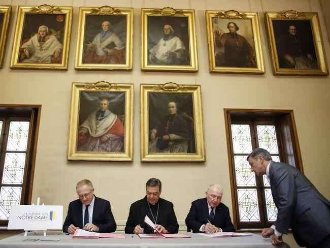 Francois-Henri Pinault, left, his father Francois Pinault, right, and Archbishop of Paris, Michel Aupetit, centre, sign an agreement to raise money to rebuild Notre Dame. Picture: AP/Thibault Camus