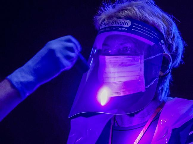Volunteers illuminated by ultra violet light to demonstrate how contamination can spread as St John Ambulance trains them to administer COVID-19 vaccines at Manchester United Football Club in England on January 30. Picture: Christopher Furlong/Getty Images