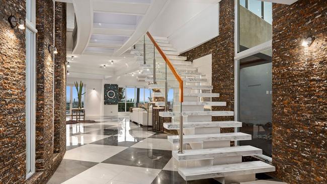 The foyer showcases a sleek marble staircase.