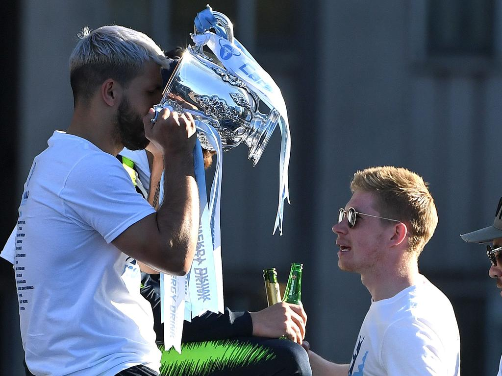 Manchester City's Belgian midfielder Kevin De Bruyne (C) reacts as Manchester City's Argentinian striker Sergio Aguero (L) drinks from the League Cup trophy during an open-top bus parade through Manchester, northern England on May 20, 2019, to celebrate winning the 2019 Premier League title, the FA Cup and English League Cup. - Pep Guardiola saluted Manchester City's history makers after they clinched the domestic treble with a swaggering 6-0 rout of Watford in the FA Cup final on Saturday. Just a week after winning a second successive Premier League crown, City's record-equalling FA Cup final victory made them the first English club to win the English title, FA Cup and League Cup in the same season. (Photo by Paul ELLIS / AFP)