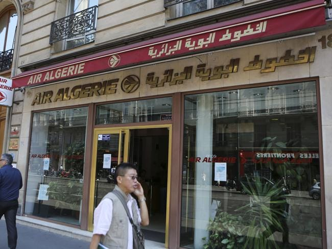 Passers-by walk past the Air Algerie company office, on the Opera Avenue in Paris. The French transport minister said there may have been 50 French nationals on the plane. Picture: Remy de la Mauviniere