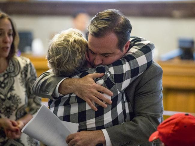Cincinnati mayor John Cranley hugs a member of Kyle Plush's family before council's Law and Public Safety Committee meeting.