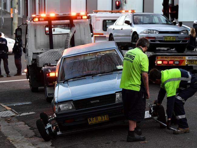 Police oversee as a car is removed from outside a crime scene in Surry Hills, Sydney. Picture: AAP Image/Joel Carrett.