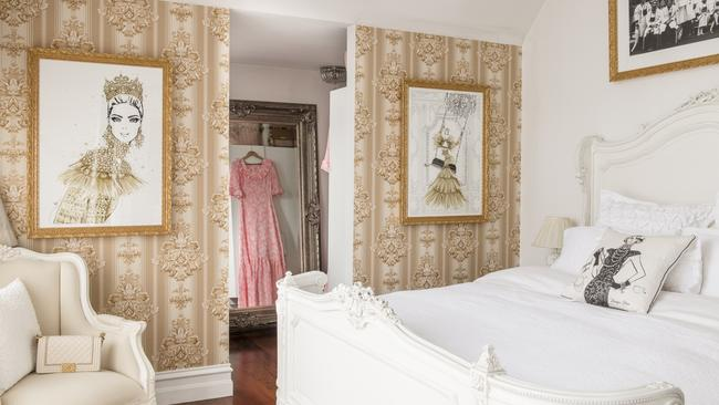 Baroque-style wallpaper and a white timber carriage-like bed bring a French salon feel to the main bedroom.