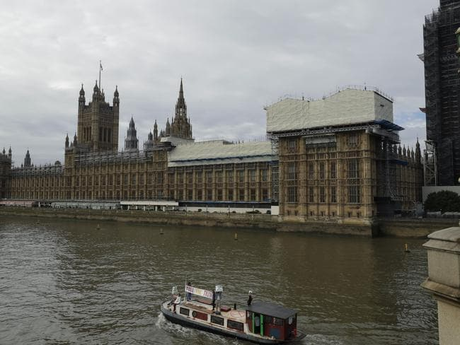 "The boat with a banner saying ""Tell the Truth"" passes Britain's Parliament. Picture: AP/Matt Dunham."